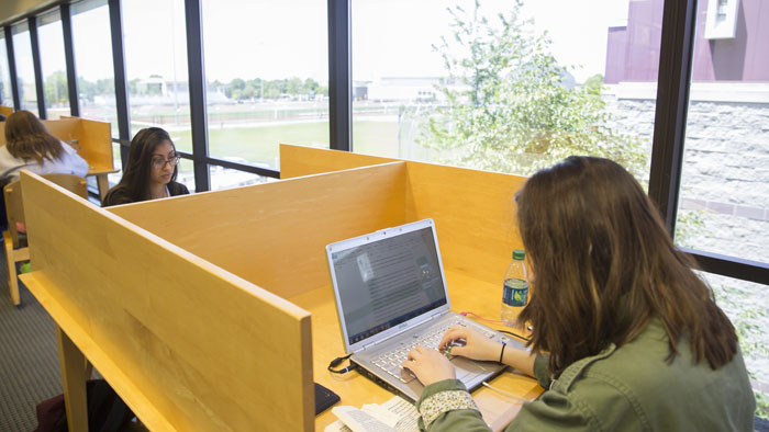 Student studying with a laptop in a carrel near an exterior window